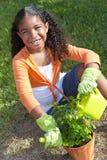 Afroamerikaner-Mädchen-Kind, das mit Blumen im Garten arbeitet Stockbild