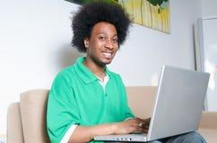 Afroamerikaner mit Laptop im Wohnzimmer Lizenzfreie Stockfotos