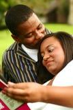 Afroamerikaner-Paar-Lesebuch im Freien stockfotografie
