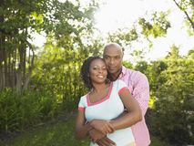 Afroamerikaner-Paare, die im Garten umfassen lizenzfreies stockbild
