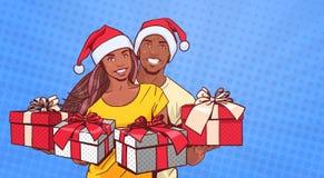 Afroamerikaner-Paare, die Santa Hats Hold Presents Happy-Mann und -frau über komischem Knall Art Background tragen lizenzfreie abbildung