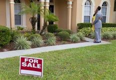 Afroamerikaner-Paare neben Haus für Verkaufs-Zeichen Stockfotos