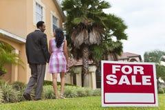 Afroamerikaner-Paare neben Haus für Verkaufs-Zeichen Stockfoto