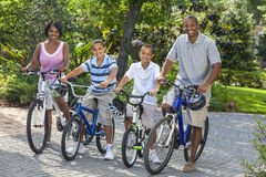 Afroamerikaner Parents die Jungen-Kinder, die Fahrräder reiten Stockfotografie