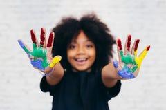 Afroamerikaner spielerisch und kreatives Kind, das Hände schmutzig mit vielen Farben erhält stockfoto