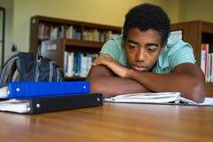 Afroamerikaner-Student, der Probleme mit Schularbeit hat Stockfoto