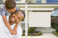 Afroamerikaner-Vater und Mischrasse-Sohn vor leerem Rea Lizenzfreie Stockfotografie