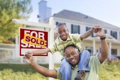 Afroamerikaner-Vater und Sohn, Verkaufszeichen und Haus Stockfotos