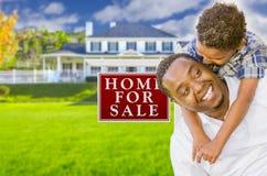 Afroamerikaner-Vater und Sohn vor Verkaufs-Zeichen und Haus Stockbilder
