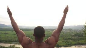 Afroamerikanerbodybuilder mit dem perfekten Körper, der auf die Bergspitze während seines Trainings des Morgens im Freien ausdehn