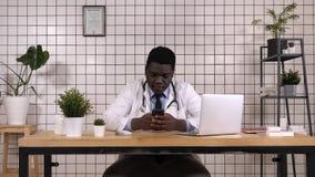 Afroamerikanerdoktor, der das intelligente Telefonsimsen hält stockfoto