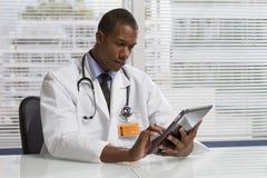 Afroamerikanerdoktor, der die elektronische Tablette, horizontal verwendet Lizenzfreies Stockfoto
