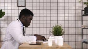 Afroamerikanerdoktor, der an Laptop arbeitet stock video