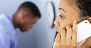 Afroamerikanerdoktor, der Telefon im Büro verwendet Stockbild