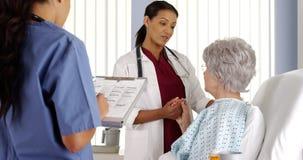 Afroamerikanerdoktor und -krankenschwester, die mit älterem Patienten sprechen Stockfotos