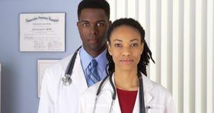 Afroamerikanerdoktoren im Krankenhaus, das Kamera betrachtet Stockbild