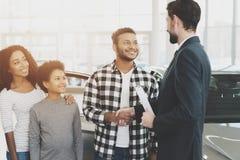 Afroamerikanerfamilie am Auto-Vertragshändler Verkäufer und Mann, welche die Hände, beglückwünschend mit Neuwagen rüttelt stockfotografie