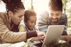 Afroamerikanerfamilie, die sich im Park hinlegt und L verwendet stockfotos