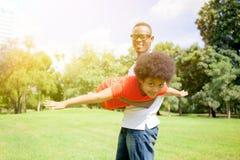 Afroamerikanerfamilie, die Spaß im Park im Freien während des Sommers hat lizenzfreies stockbild