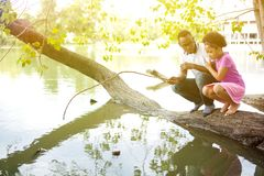 Afroamerikanerfamilie, die um den See spielt stockfotos