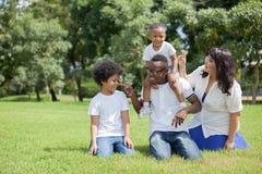 Afroamerikanerfamilie längsseits mit der asiatischen Mama, die spielerisches a ist stockbilder