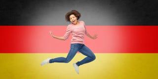 Afroamerikanerfrau, die über deutsche Flagge springt Stockbilder