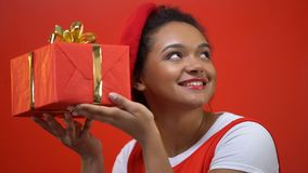 Afroamerikanerfrau, die das giftbox versucht, zu schätzen rüttelt, was inner ist, anwesend stock video footage