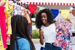 Afroamerikanerfrau, die dem Käufer Kleidung am Markt zeigt stockfoto