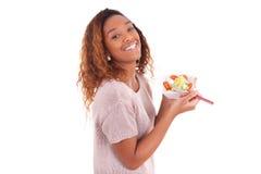 Afroamerikanerfrau, die den Salat, lokalisiert auf Weiß isst Stockfotos