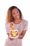 Afroamerikanerfrau, die den Salat, lokalisiert auf weißem backgroun isst Lizenzfreie Stockfotografie