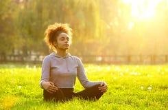 Afroamerikanerfrau, die in der Natur meditiert Stockfotografie