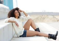 Afroamerikanerfrau, die draußen sitzt lizenzfreie stockbilder
