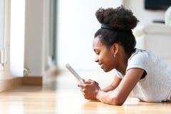 Afroamerikanerfrau, die eine Tasttablette in ihrem lebenden ro verwendet Lizenzfreies Stockbild