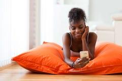 Afroamerikanerfrau, die eine Textnachricht an einem Handy sendet Lizenzfreies Stockfoto