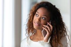Afroamerikanerfrau, die an einem Handy - schwarze Menschen spricht Lizenzfreie Stockbilder