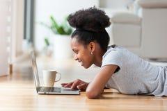 Afroamerikanerfrau, die einen Laptop in ihrem Wohnzimmer - Schwarzes verwendet Stockfotografie