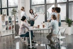 Afroamerikanerfrau, die Geschäftsseminar für ihre Kollegen im Büro zur Verfügung stellt stockfotos