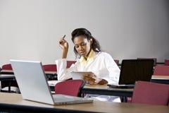 Afroamerikanerfrau, die im Klassenzimmer studiert Stockbild