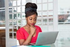 Afroamerikanerfrau, die mit Computer arbeitet lizenzfreies stockfoto