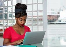 Afroamerikanerfrau, die Mitteilung mit Computer sendet lizenzfreies stockbild