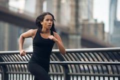 Afroamerikanerfrau, die in New York City am Morgen läuft stockbild