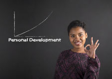 Afroamerikanerfrau mit dem perfekten Handzeichen, das persönliche Entwicklung auf Tafelhintergrund zeigt Stockfotografie