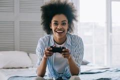 Afroamerikanerfrau mit dem Steuerknüppel, der Videospiel beim Sitzen spielt lizenzfreies stockfoto