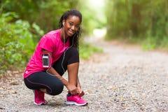 Afroamerikanerfrauenläufer, der Schnürsenkel - Eignung, PET festzieht stockfotografie