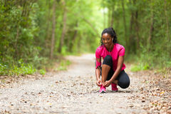 Afroamerikanerfrauenläufer, der Schnürsenkel - Eignung, PET festzieht lizenzfreie stockfotografie