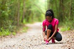 Afroamerikanerfrauenläufer, der Schnürsenkel - Eignung, PET festzieht stockfoto