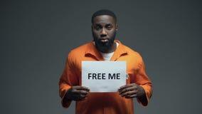 Afroamerikanergefangenholding geben mich Zeichen in der Zelle, das Unschuldig frei, das um Hilfe bittet stock video footage