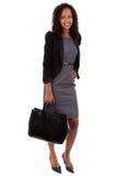 AfroamerikanerGeschäftsfrau, die eine Handtasche anhält Stockfoto