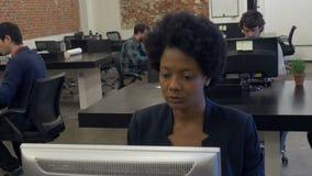 AfroamerikanerGeschäftsfrau, die Tischrechner bearbeitet stock video