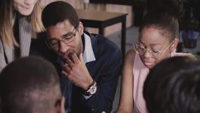 Afroamerikanergeschäftsleute lösen durch die Tabelle, hören auf europäischen weiblichen Führer bei der multiethnischen Bürositzun stock footage